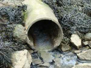 pipe with sludge flowing out onto soil and rocks